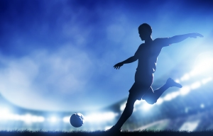 Football, soccer match. A player shooting on goal. Lights on the